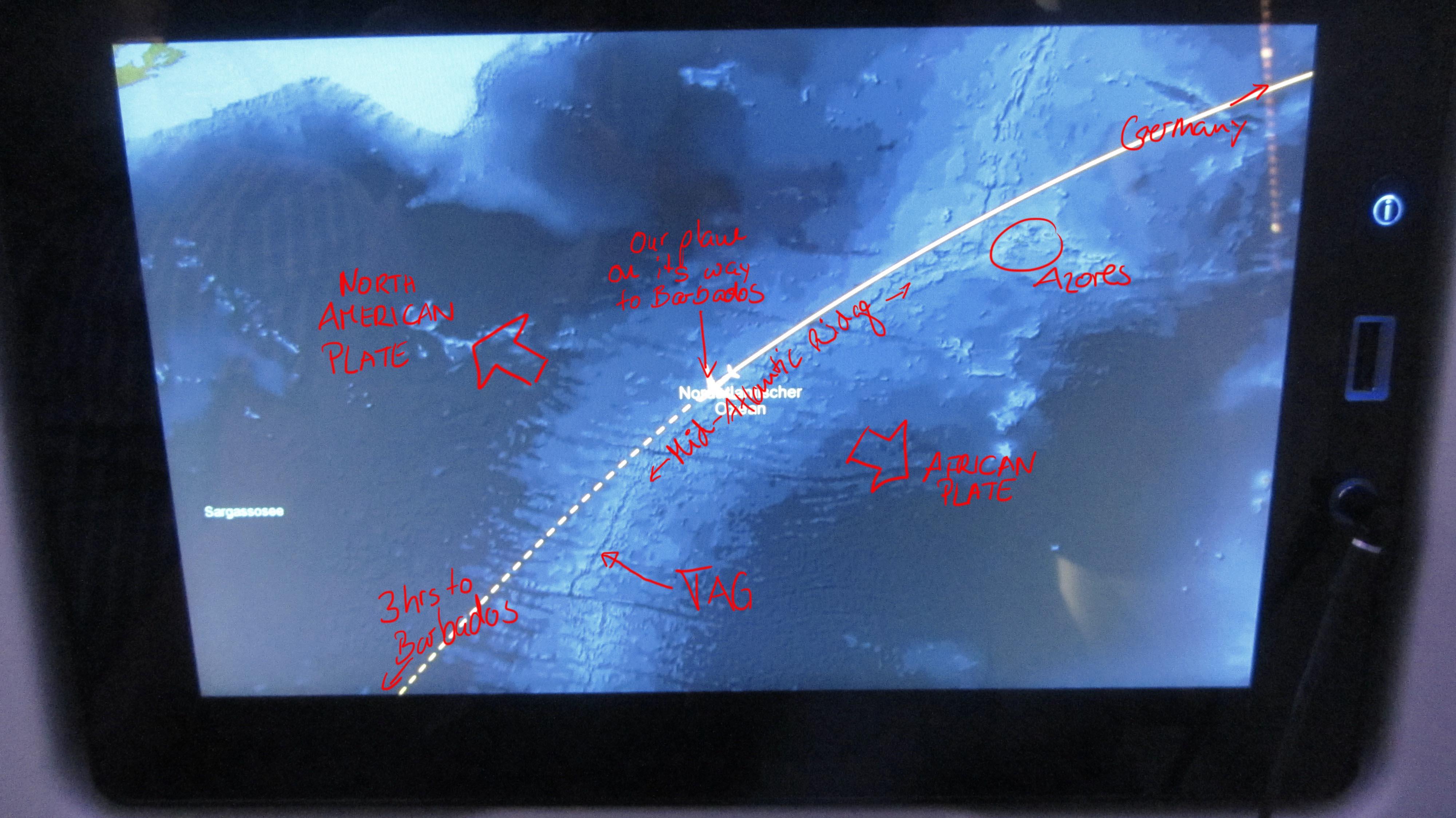 Photo of the info screen on our flight to Barbados with some remarks on what marine geologists see on it: The Mid-Atlantic Ridge (in pale blue colours, as it is shallower than the deep sea plains in dark blue) is a boundary, at which two tectonic plates spread apart. The North American plate, including the continent, moves with a rate of 1cm per year west, while the African and Eurasian plate move with also about 1 cm per year eastwards. The TAG hydrothermal field lies on the plate boundary, which is visible as a fine blue line, due to a graben structure, the so-called rift valley, on top of the Mid-Atlantic Ridge. / Foto vom Infobildschirm auf unserem Flug nach Barbados mit einigen Anmerkungen, was Meeresgeologen darauf sehen: Der Mittelatlantische Rücken (als hellblaues Band gut sichtbar, weil er sich von den tiefer gelegenen Tiefseeebenen in dunkelblau abhebt) ist eine Grenze, an der zwei tektonische Platten auseinander spreizen. Die Nordamerikanische Platte, inklusive des Kontinents, bewegt sich mit rund 1 cm pro Jahr nach Westen, während die Eurasische und Afrikanische Platte mit ebenfalls 1 cm pro Jahr nach Osten driften. Das TAG Hydrothermalfeld liegt genau auf der Plattengrenze, die als feine, dunkelblaue Linie auf dem Mittelatlantischen Rücken sichtbar ist, weil sich dort ein tiefer gelegener Graben befindet, das so genannte Rift Valley. (© Meike Klischies)