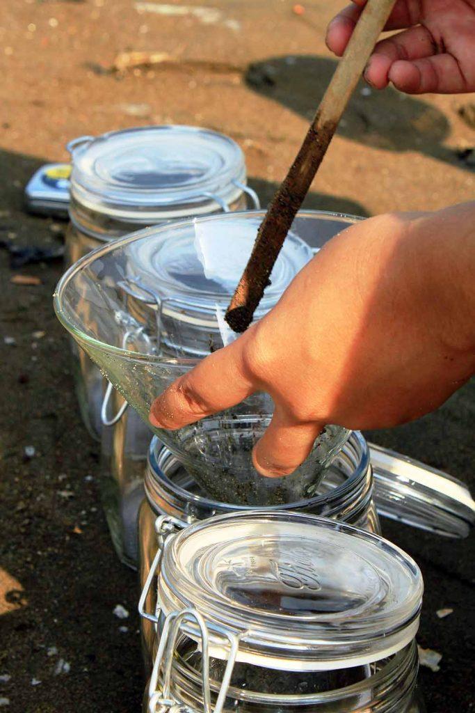 Das Sediment wird dann in Glasbehälter umgefüllt und ins Labor transportiert. Dabei gilt es, den Eintrag von Plastikfasern, beispielsweise aus der eigenen Kleidung, möglichst zu verhindern. Foto: GAME