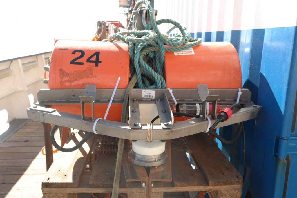 An OBS on the working deck of RV Merian. The orange cylinders are the floatations which make sure that the instrument will come back to the surface. Photo: Martha Deen
