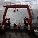 Fast fünf Minuten lang wurde die Dredge (blaues Netz) über den Meeresboden hinter dem Schiff hergezogen. Hier sieht man, wie sie an Deck geholt wird. Foto: G. Seidel, GEOMAR