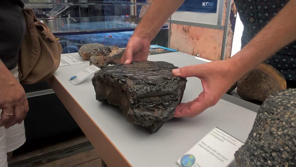 Daraus besteht der Boden der Ozeane: Basalt. Einige Kanten sind so scharf, dass sich der präsentierende Wissenschaftler daran geschnitten hat. Photo: Jill Alina Koenig