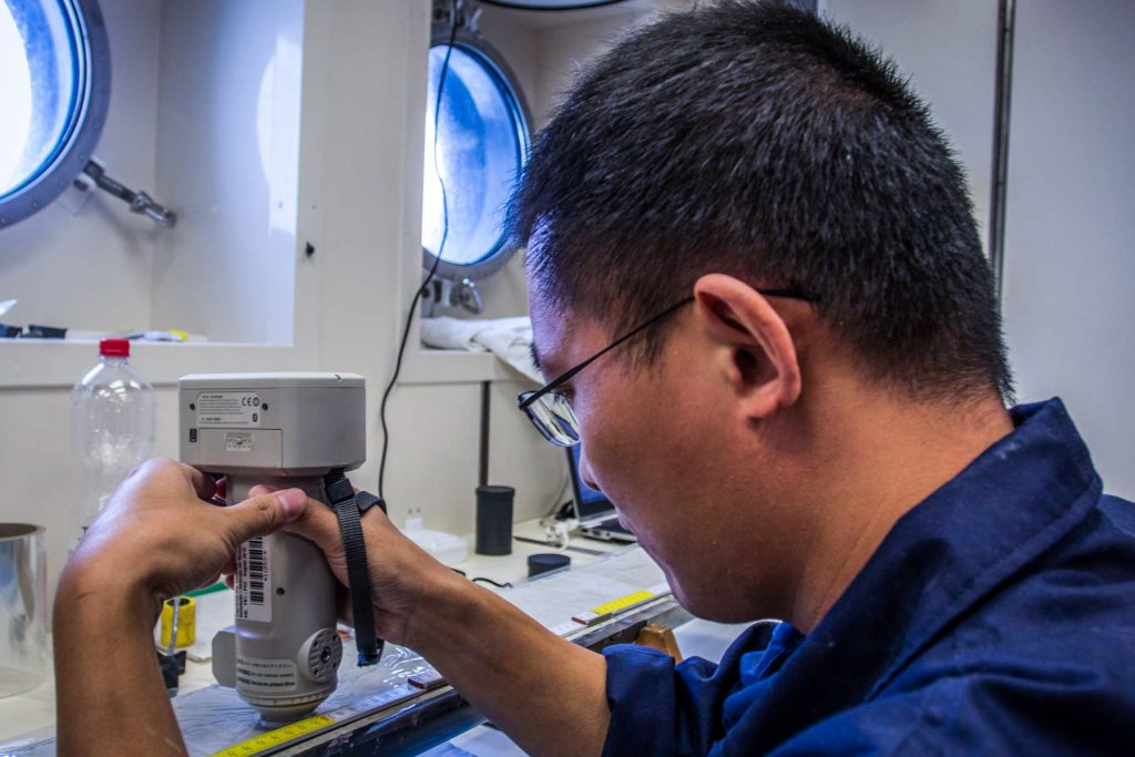 Jianxing Liu (FIO) analyzing a carbonate-rich core from 1771 m water depth for it's specific color-spectrum. Photo: Thomas Ronge, editing: Steffen Niemann